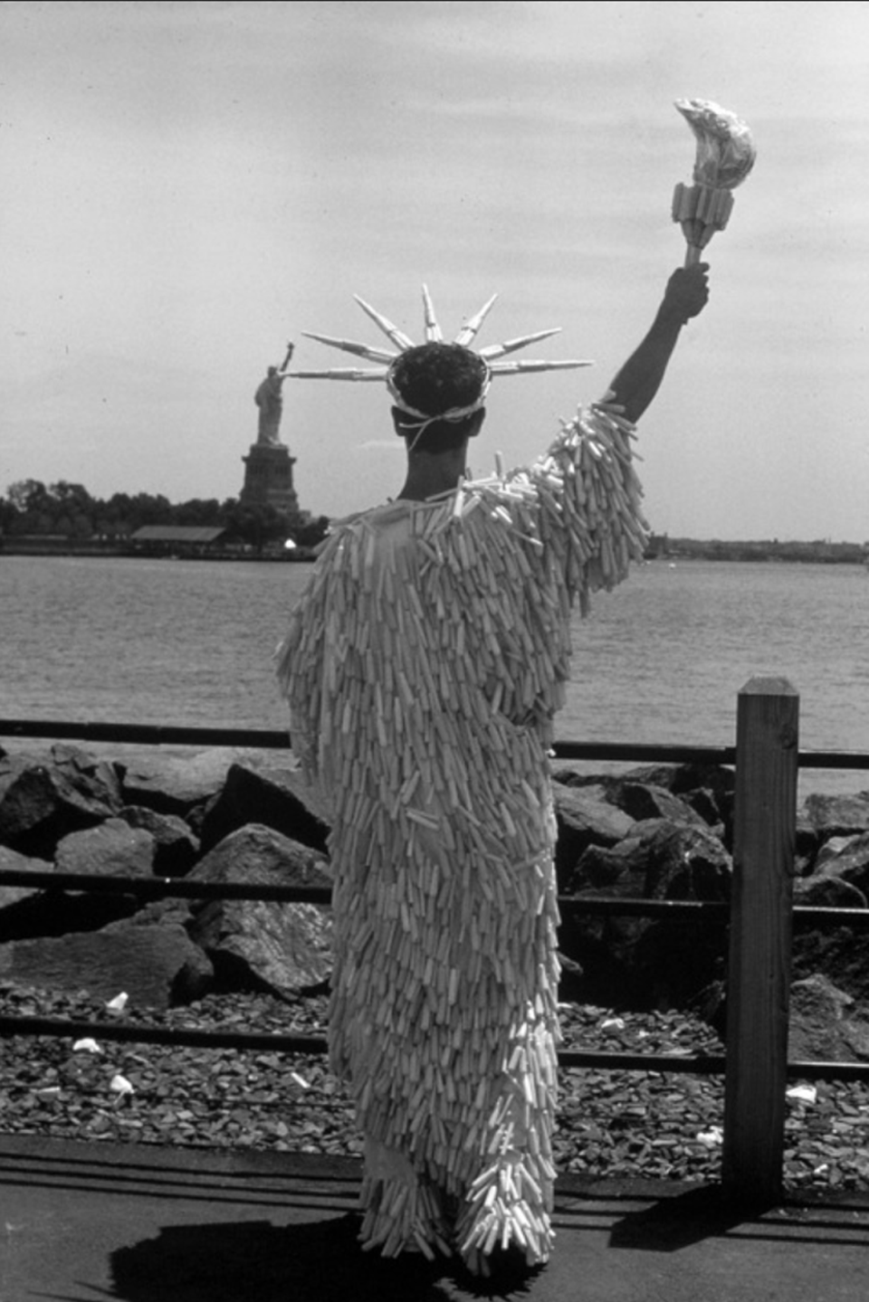 Miss Tampon Liberty, artist at Liberty State Park, NJ, with gown of 3,000 plastic tampon applicators washed up on beaches, 1989.