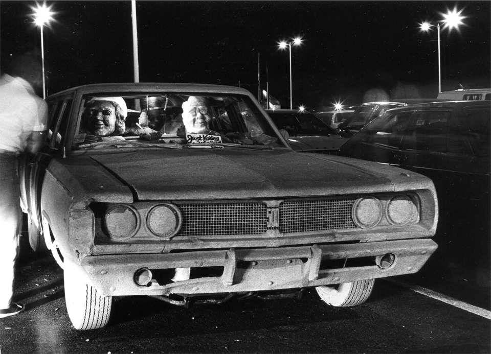 "Just Visiting for the Weekend, with the Sand Family (Ron & Nancy Reagan), Sand Car Series, MacMillan Wharf Parking Lot ""Gallery,"" 1982. Photo: Rachel Giese Brown."